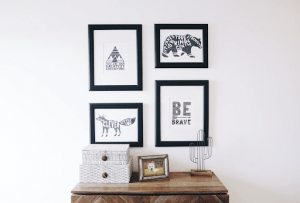 four framed pictures on the wall of a luxury home with motivational quotes and a framed dog picture and cactus figurine below it can serve as a gift for father's day this year | Luxury Homes by Brittany Corporation