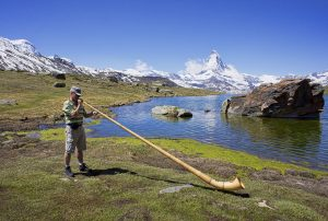 One of the most iconic sounds in Swiss-German music is the Alphorn as used by an Alphorn player with the Swiss Alps as the background. | Luxury Homes by Brittany Corporation