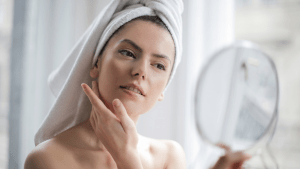 Woman checking out her facial features for skincare in the bathroom   luxury lifestyle and home by Brittany Corporation