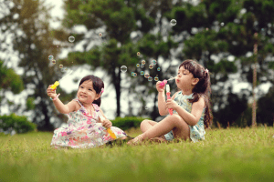 children blowing bubbles in front of a pine tree forest
