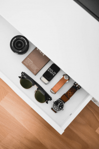 A drawer containing sunglasses, watches, and a camera lens   Luxury Homes by Brittany Corporation
