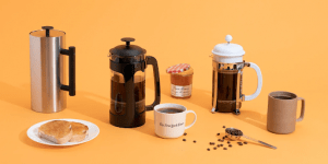 A french press on a yellow studio background | Luxury Homes by Brittany Corporation