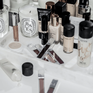 An array of various makeup items on a white marble table