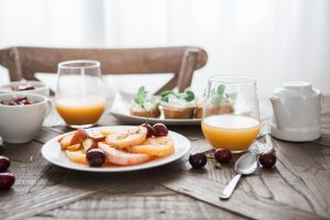 Breakfast table of fruits vegetables bread and fruit juices condo living guide | Luxury Homes by Brittany Corporation