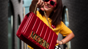 Red Moschino designer bags held by brunette with red sunglasses on | Luxury Homes by Brittany Corporation