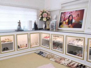 Chic and girlywhite and pink walk in closet with flowers and framed photo.