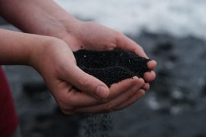 Holding soil in hands perfect for composting in order to grow healthy plants | Luxury Homes by Brittany Corporation