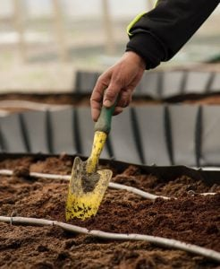 Mini shovel digging soil to composte for healthy plants | Luxury Homes by Brittany