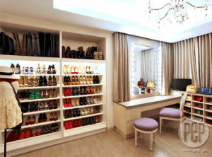 Modern and elegant walk in closet in neutral colors with vanity.