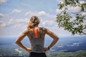 White woman taking in view after jogging on an elevated trail. Jogging requires you to increase your amount of drinking water   Luxury Homes by Brittany Corporation