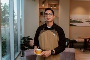 Man with brown apron holds barista-style mug at home | Luxury Homes by Brittany Corporation