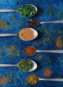 6 spices on silver spoons over a blue textured background | luxury home by brittany corporation