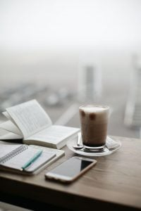 A table in a luxury condominium with a book, notebook, pen, phone, and barista-style mug | Luxury Homes by Brittany Corporation