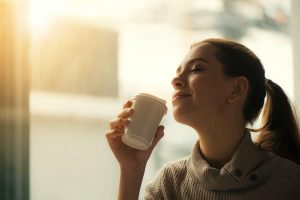 Woman smelling tea inside her luxury house and lot | Luxury properties by Brittany Corporation