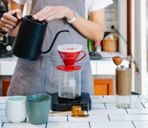 Woman making pour over tea in her luxury condominium | Luxury Homes by brittany corporation