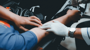 Doctor checking pulse of man's arm while on stretcher