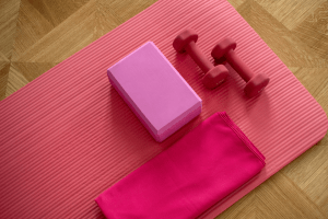 Pink indoor gym workout essential equipment including barbels, yoga block, yoga mat, and towel.