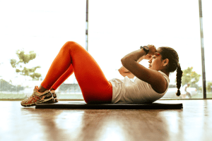 Girl working out with her body weight indoors on her yoga mat | luxury homes by brittany corporation