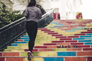girl running up colorful stairs outdoors for fitness and health and to burn calories | luxury homes by brittany corporation