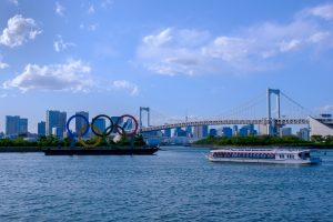 Olympics symbol in Odaiba, Japan with cityscape and cruise.