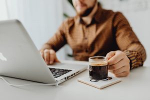 pandemic response: work from home guy with mug of shot of espresso coffee | luxury lifestyle and homes by brittany corporation