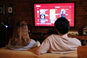 A couple of teenagers watching movies on TV in the living room as a pandemic response | luxury lifestyle and homes by brittany corporation