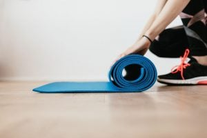 Sporty girl rolling yoga mat for exercise use as a pandemic response | luxury lifestyle and homes by brittany corporation