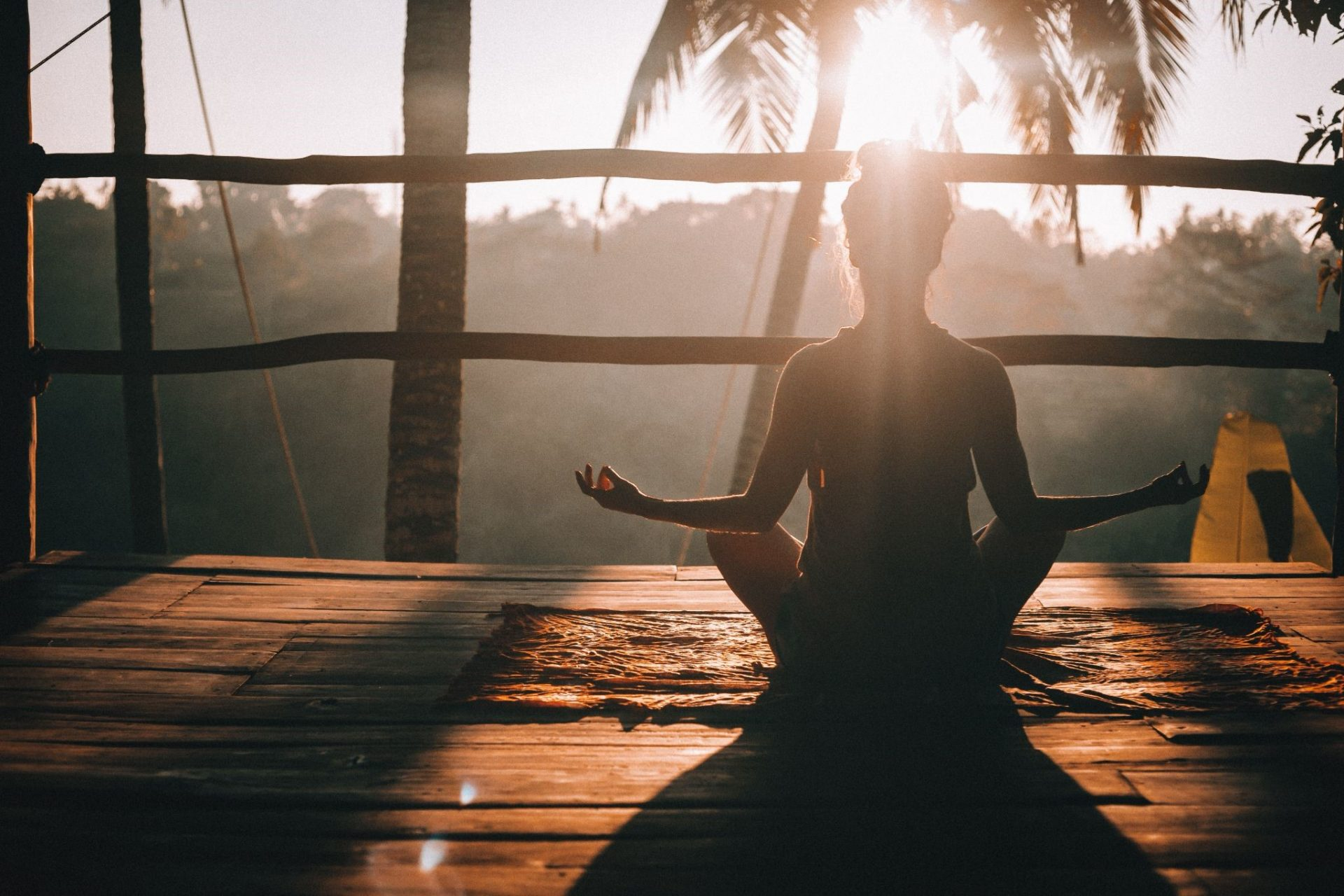 silhouette of girl meditating and doing a yoga pose in an island | luxury lifestyle and homes by brittany corporation