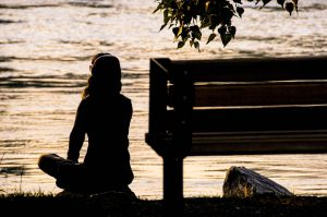 silhouette of girl meditating by the lake next to a bench in nature   luxury lifestyle and homes by brittany corporation