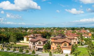 An spacious sprawling wide area of an italian inspired subdivision with clean beautiful houses and lots in warm welcoming colors, classic accents, pine trees, lush greenery, healthy grass, and gates of rustic bricks
