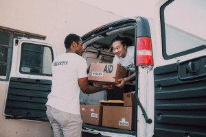 asian and black male humanitarians wearing volunteer shirts to donate to the needy | luxury homes by brittany corporation