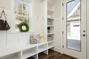 A landscape photo of a clean and spacious mudroom with white paintwork, wooden floor and cubbies, and a clear, glass door. | luxury homes by brittany corporation