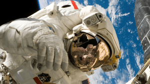 astronaut in the outer space race showing planet earth | luxury homes by brittany corporation