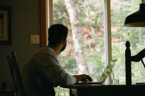 A back-view photo of a man wearing a gray sweater; the backdrop consists of an outdoor view of an indoor home office.