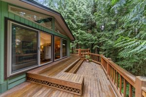 A landscape view of a hardwood house porch home features, surrounded by lush pine trees.