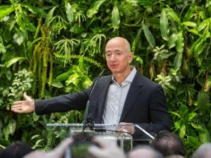 Jeff Bezos explaining the space race with a background of sustainable plants in a conference | luxury homes by brittany corporation