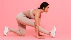 Woman in pink sportswear doing stretching exercises to work out at her luxury home - Brittany Corporation
