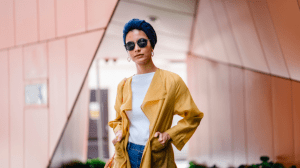 Woman in yellow trench coat with sunglasses and confidently flaunting her style tips - Brittany Corporation