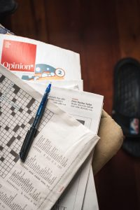 pen on newspaper crosswords on stack of magazines at home | luxury homes by brittany corporation