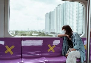 Woman sitting in a train overlooking a luxury condominium | Luxury Homes by Brittany Corporation