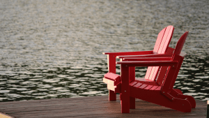 two retirement red wooden chairs benches on a wooden platform overlooking a lake for retirement places | luxury homes by brittany corporation