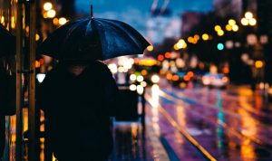 person with umbrella showing city lights at night   luxury homes by brittany corporation