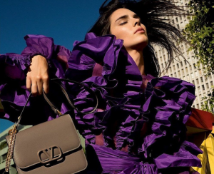 Brunette Lady wearing a purple ruffled blouse while holding a brown valentino bag | luxury homes by brittany corporation