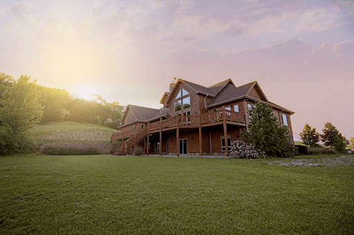 Red country home in a green field of grass | luxury homes by brittany corporation