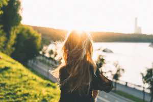 blonde lady standing against the setting sun   luxury homes by brittany corporation