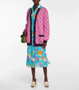 Dark-skinned woman wearing a blue floral dress with a pink monogrammed cardigan. | luxury homes by brittany corporation