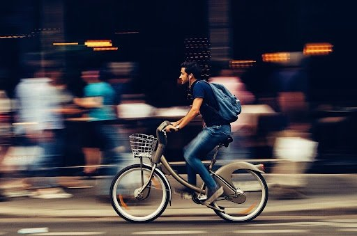 South Asian Man riding a bike on his way to his luxury home on a busy street with blurred people behind him | luxury homes by brittany corporation