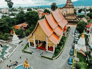 Chiang Mai Thailand best vegan travel destination building with orange high roof with tourists around the temple   luxury homes by brittany corporation