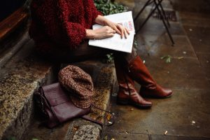 Woman in red sweater and some paper on her lap she wears brown leather boots and luxury home in cap crosswinds tagaytay   Luxury homes by brittany corporation