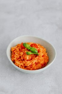 a bowl of red swiss risotto with a basil on top in a white bowl on a marble counter top in a luxury mansion   Luxury homes by brittany corporation